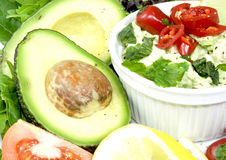 Guacamole. In a bowl, decorated with avocado halves, lemon and lime slices, red chili peppers, tomato quarters and salad Stock Image