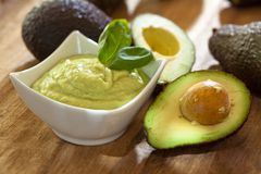 Guacamole. Avocado mousse with halved avocados Stock Photos