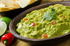 Guacamole. A bowl of creamy guacamole with avocado, tomato, cilantro, lime and tortilla chips Royalty Free Stock Photography