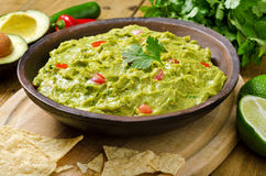 Guacamole. A bowl of creamy guacamole with avocado, tomato, cilantro, and lime with tortilla chips Stock Image