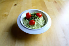 Guacamole. Decorated with cherry tomatoes and herbs in a white bowl royalty free stock images