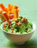 Guacamole. Healthy avocado guacamole served with carrot sticks Royalty Free Stock Images