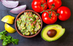 Guacamole And Ingredients - Avocado, Tomatoes, Onion, Cilantro Dark Background.