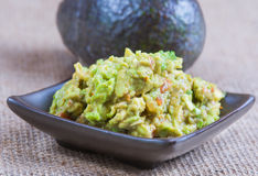 Guacamole and avocado. Guacamole in brown dish with avocado in background Royalty Free Stock Image