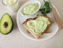 Guacamole with avocado, fresh cheese and parsley on slice of bread stock photography