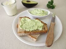 Guacamole with avocado, fresh cheese and parsley on slice of bread stock image