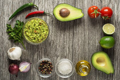 Guacamole. Avocado guacamole with fresh ingredients on wooden table royalty free stock images