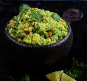 Guacamole. With avocado, lime, tomato and cilantro with tortilla chips royalty free stock image