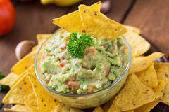 Guacamole avocado, lime, tomato, onion and cilantro, served with nachos Stock Photos