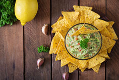Guacamole avocado, lime, tomato, onion and cilantro, served with nachos. Traditional Mexican snack. Top view Royalty Free Stock Photo