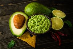 Guacamole in blue bowl with tortilla chips and lemon on natural wooden desk. royalty free stock image
