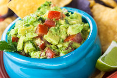 Guacamole Bowl with Chips. Bowl of chunky guacamole with tortilla chips and a slice of lime Royalty Free Stock Photography