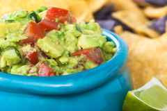 Guacamole Bowl Closeup. Bowl of chunky guacamole with tortilla chips and a slice of lime Stock Photography