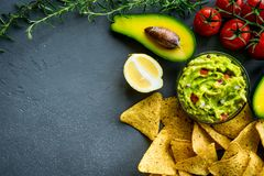 Guacamole bowl with ingredients and tortilla chips on a stone table. Top view image. Copyspace for your text. Guacamole bowl with ingredients and tortilla chips Stock Photo