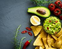 Guacamole bowl with ingredients and tortilla chips on a stone table. Top view image. Copyspace for your text. royalty free stock photography