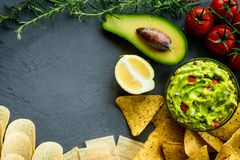 Guacamole bowl with ingredients and tortilla different tipes of chips on a stone table. Top view image. Copyspace for. Your text Stock Photography