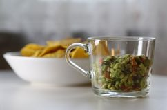 Guacamole with a Bowl of Nachos. Mexican guacamole with corn nachos. The guacamole is homemade, fresh and delicious and it`s in the foreground of this photo stock photography