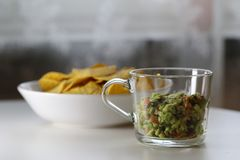 Guacamole with a Bowl of Nachos. Mexican guacamole with corn nachos. The guacamole is homemade, fresh and delicious and it`s in the foreground of this photo stock images