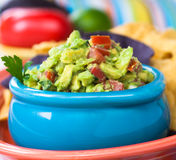 Guacamole Bowl. Tasty guacamole bowl with chips and fresh ingredients on the side Stock Photo