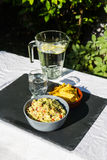 Guacamole in bowl with tortilla chips and iced water. Outdoors o Royalty Free Stock Photo