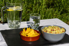 Guacamole in bowl with tortilla chips and iced water. Outdoors o Royalty Free Stock Image
