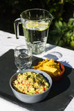 Guacamole in bowl with tortilla chips and iced water. Outdoors o Royalty Free Stock Images