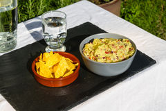 Guacamole in bowl with tortilla chips and iced water. Outdoors o Royalty Free Stock Photography