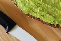 Guacamole and bread. Toast with avocado on wooden cutting board with knife. royalty free stock photos