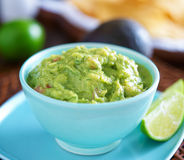 Guacamole. In colorful blue bowl with tortilla chips royalty free stock photos