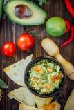 Guacamole com microplaquetas de milho - nachos, feitos do abacate, dos tomates e do cal imagem de stock royalty free