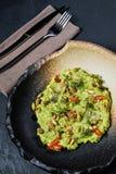 Guacamole con los cacahuetes asados, fondo negro, visión superior fotografía de archivo