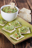 Guacamole with crackers. Bowl with freshly made guacamole and crackers. Shallow dof stock photos