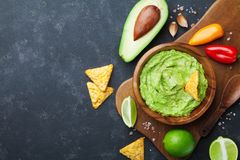 Guacamole dip with avocado, lime and nachos on black table top view. Copy space.Traditional mexican food. Guacamole dip with avocado, lime and nachos on dark stock photography