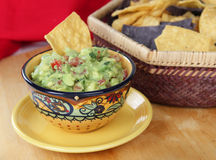 Guacamole Dip with Chips. Bowl of guacamole dip with basket of tortilla chips Stock Image