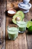 Guacamole dip style green vegetables smoothie. In glasses with ingredients avocado and lime on rustic wooden table, savory healthy dairy drink with organic Royalty Free Stock Photography