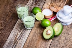 Guacamole dip style green vegetables smoothie. In glasses with ingredients avocado and lime on rustic wooden table, savory healthy dairy drink with organic Royalty Free Stock Images