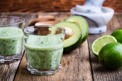 Guacamole dip style green vegetables smoothie. In glasses with ingredients avocado and lime on rustic wooden table, savory healthy dairy drink with organic Royalty Free Stock Photo