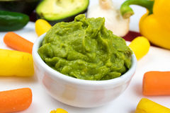 Guacamole Dip Surrounded by colorful vegetables and ingredients. Image showing fresh guacamole in a white ceramic bowl which is surrounded by vibrant yellow and stock image