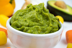 Guacamole Dip Very Closeup Surrounded by colorful vegetables and ingredients. Close view image showing fresh guacamole dip in a white ceramic bowl with yellow royalty free stock images