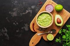 Guacamole e ingredientes do guacamole no fundo de mármore preto Vista superior, espaço da cópia fotografia de stock royalty free