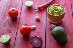 Guacamole e ingredientes Fundo vermelho Culin?ria mexicana imagens de stock