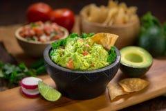 Guacamole fatto a mano premio dagli avocado organici freschi con i chip su una tavola con la salsa di pico de Gallo Immagini Stock