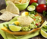 Guacamole fresco com as microplaquetas de tortilha do milho foto de stock