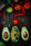 Guacamole and fresh avocado on wooden table. Stock Photos
