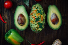 Guacamole and fresh avocado on wooden table. Stock Images