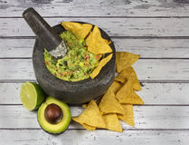 Guacamole in granite molcajete mortar on old wooden background Royalty Free Stock Photography