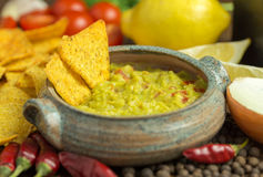 Guacamole in home crafted bowl with tortilla chips around. Stock Image