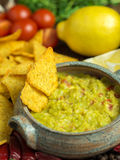Guacamole in home crafted bowl with tortilla chips around. Royalty Free Stock Photos