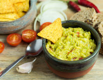 Guacamole in home crafted bowl with tortilla chips. Stock Photos