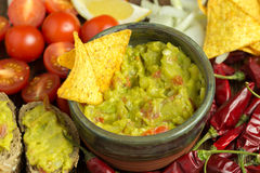 Guacamole in home crafted bowl with tortilla chips inside. Royalty Free Stock Photos